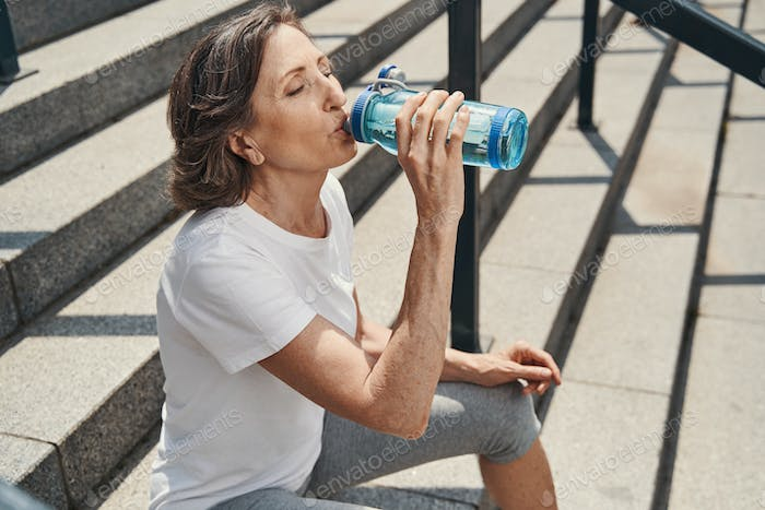 Active aged woman quenching thirst on steps