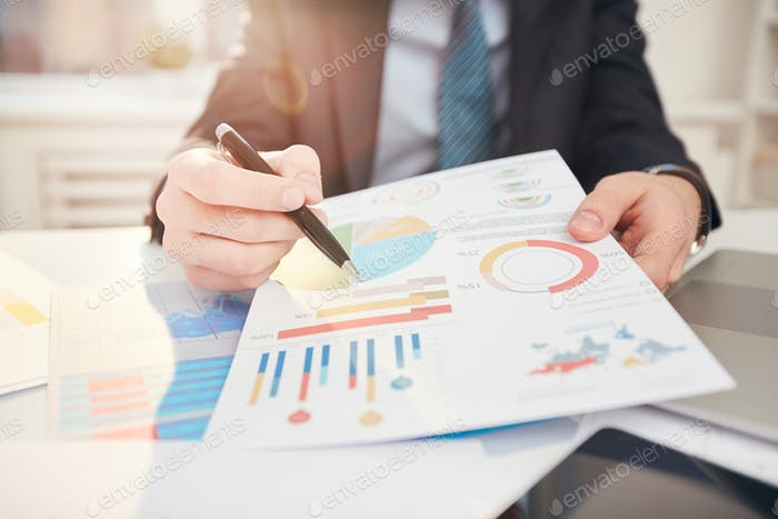 Businessman Pointing at Statistics Data Close up