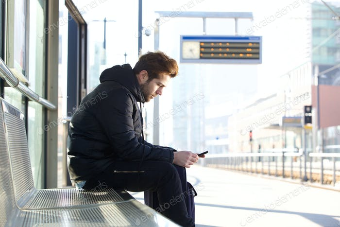 Man sitting on bench at train station platform with mobile phone