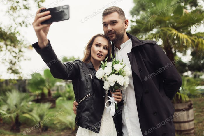 Young attractive man in trench coat and beautiful woman in black
