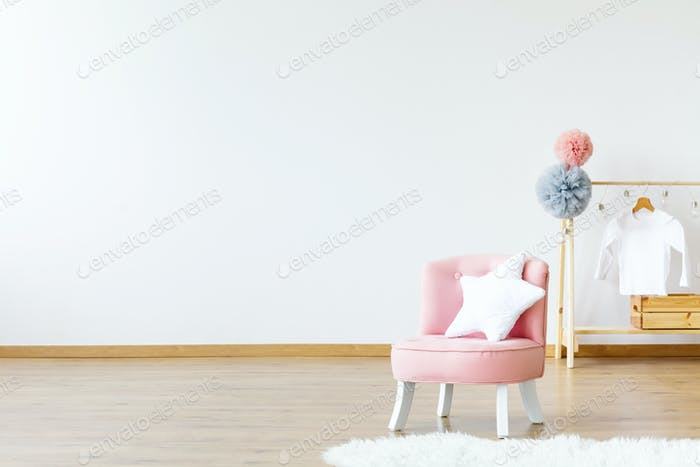 Pink chair with star shaped cushion standing in bright baby room