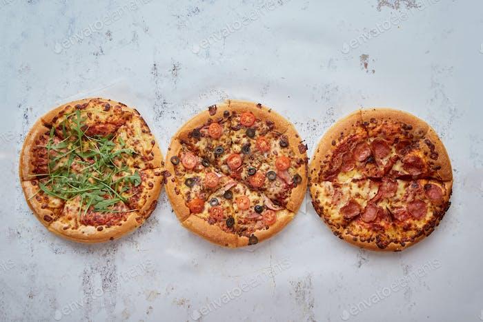 Drei verschiedene Arten von Pizzen in einer Reihe auf weißem rostigen Tisch platziert
