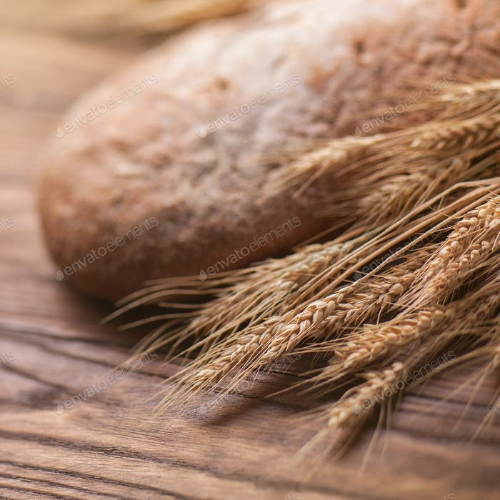 wheat and bread on wooden table, shallow DOF