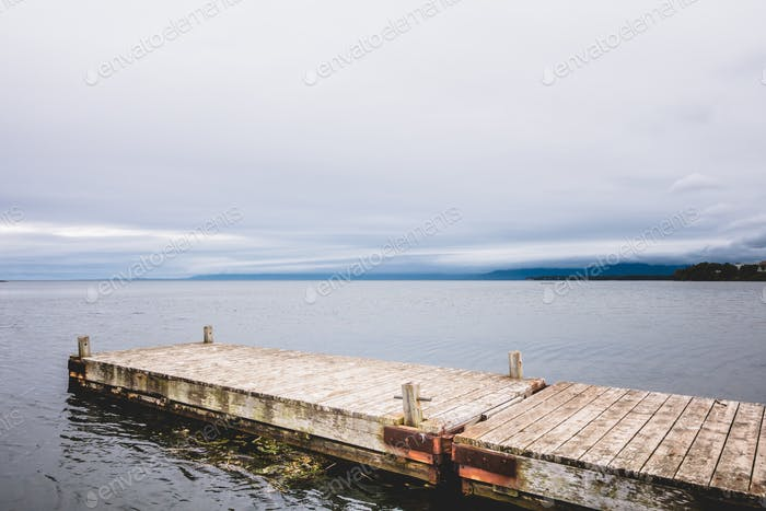 Wooden pier at ocean in cloudy day in Gaspe.