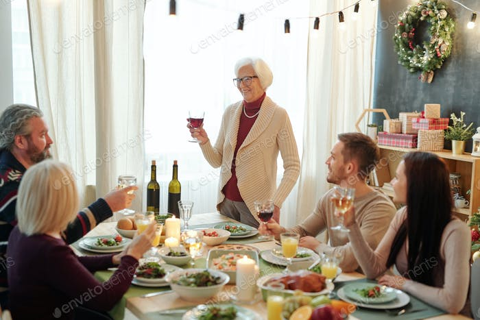Smiling senior woman holding glass of red wine while toasting by served table