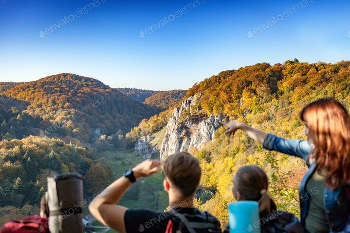 Group of people with backpacks looking at beautiful landscape view in the mountain