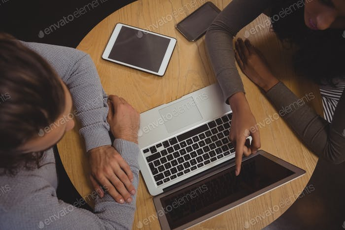 Woman with friend pointing at laptop