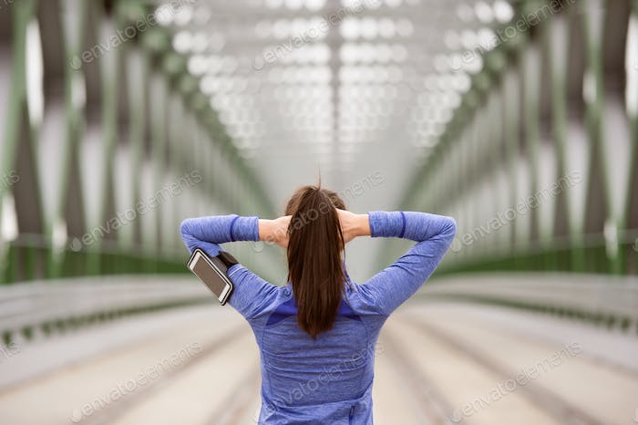 Young runner in the city stretching on green steel bridge