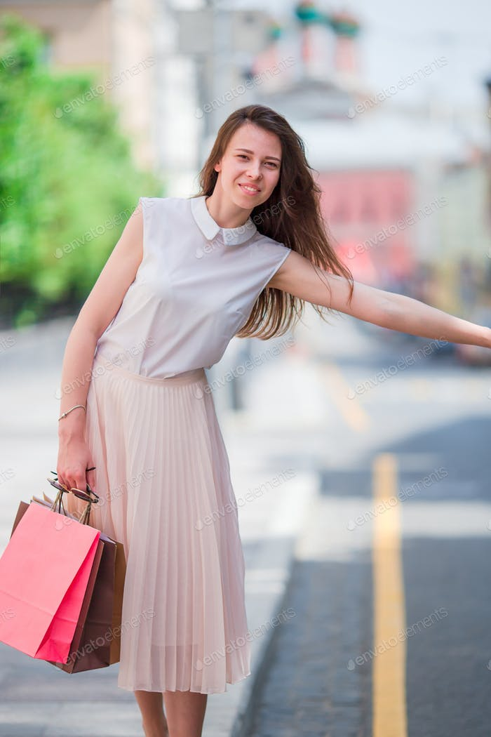 Young happy girl with shopping bags catch a taxi. Portrait of a beautiful happy woman standing on