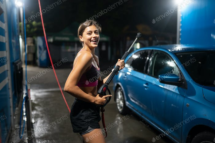 Junge Frau wäscht blaues Auto bei Autowäsche