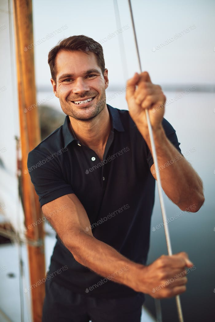 Smiling young man standing by ropes on his yacht