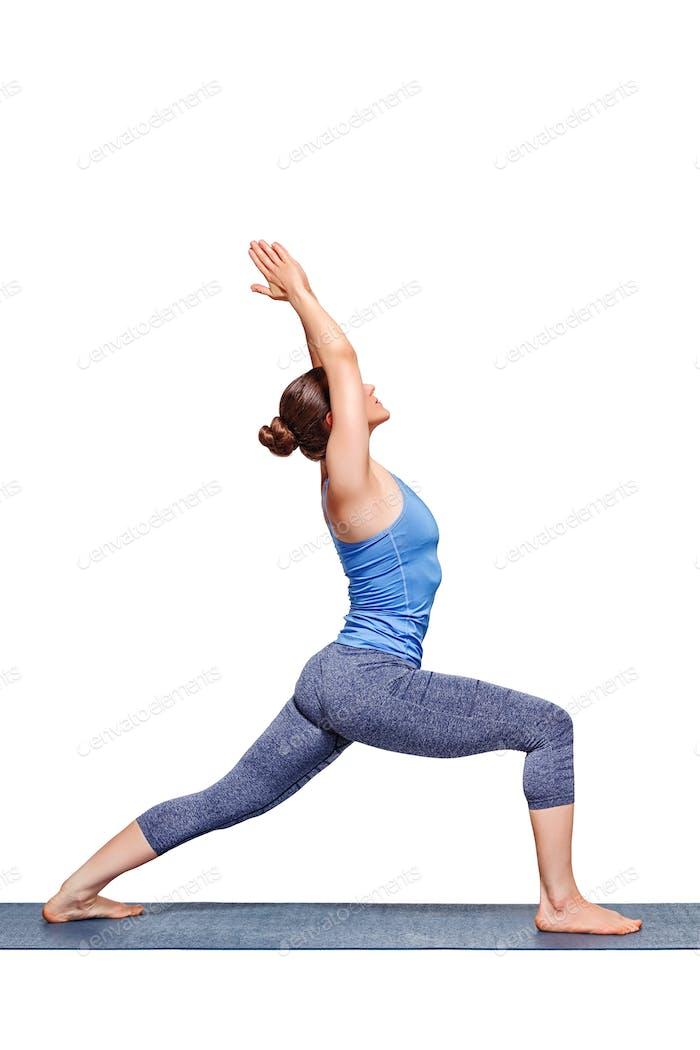 Sporty fit yogini woman practices yoga asana utthita Virabhadras
