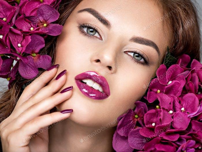 Frau mit lila Make-up von Lippen und Fingernägeln