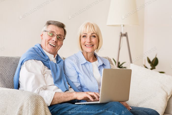 Happy mature couple with laptop computer smiling to camera
