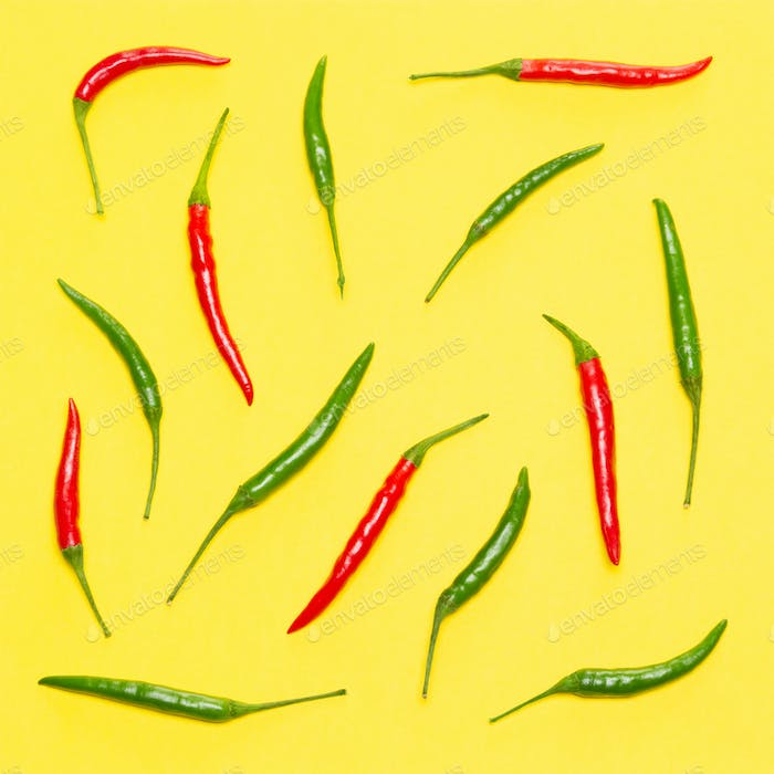 Red and green chili peppers on yellow background