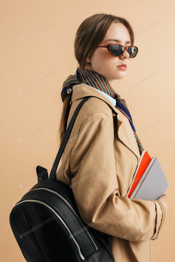 Young stylish girl in trench coat and sunglasses with backpack and notepads looking aside