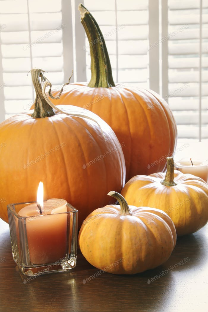 Pumpkins with candle on table near window