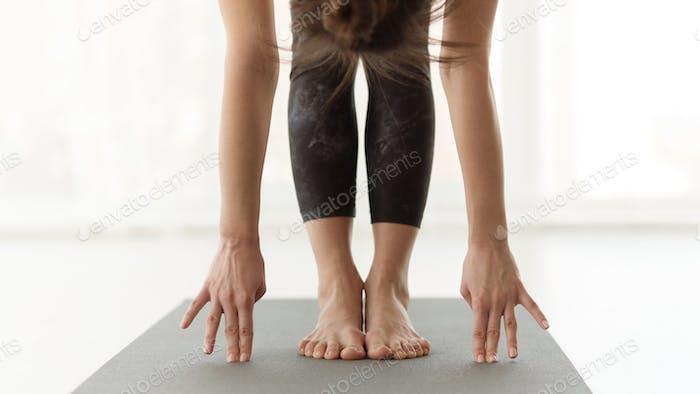 Young yogi woman practicing yoga, hands to teet pose