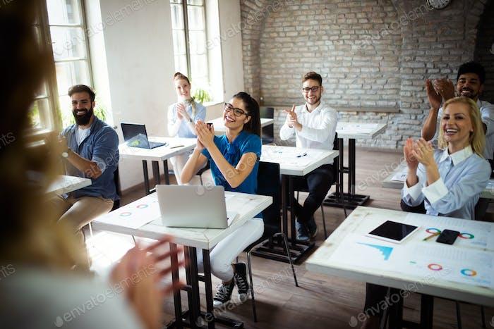 Erfolgreiche glückliche Gruppe von Menschen, die Software Engineering und Business während der Präsentation lernen