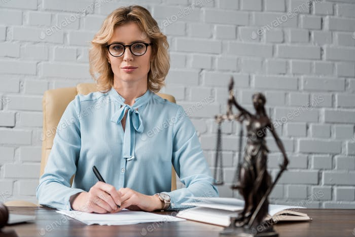 confident female lawyer in eyeglasses sitting at workplace and looking at camera