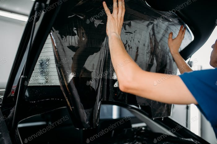 Male worker applying car tinting film