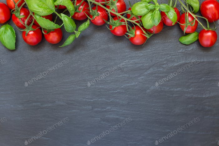 Cherry tomatoes with basil leaves on a dark slate background, ho