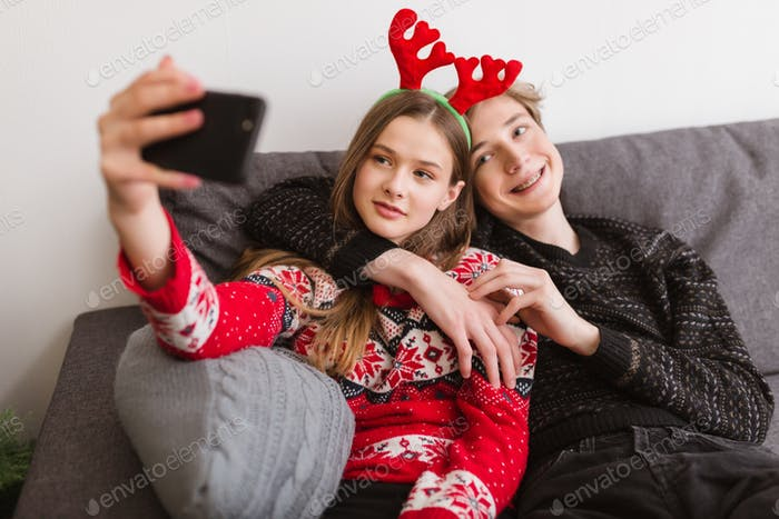 Young smiling couple sitting on sofa at home and taking funny selfie while spending time together