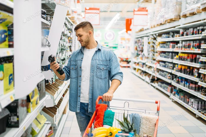 Man choosing electric screwdriver in supermarket