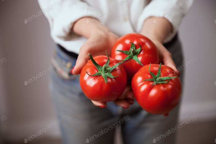 Young woman hands with tomatoes