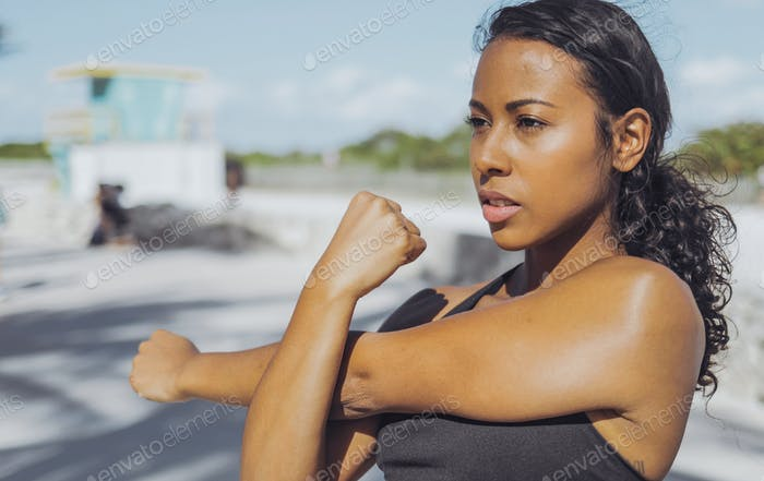 Pretty black girl warming up in park