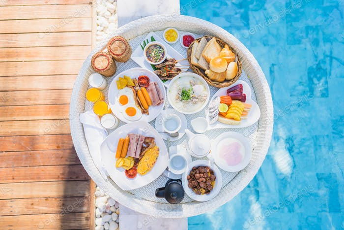 Floating breakfast set in tray with fried egg omelette sausage ham bread fruit milk juice coffee
