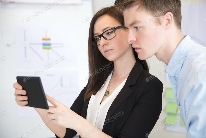 Businesswoman Using Tablet Computer With Male Colleague