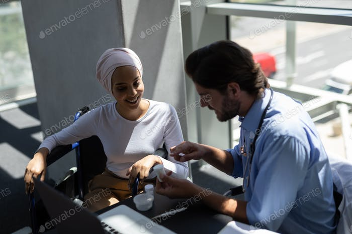Male doctor with smiling disable woman discussing over medicines in hospital