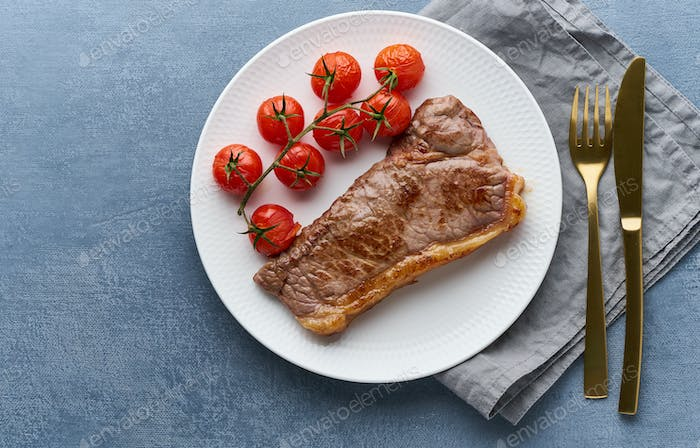 keto ketogenic diet steak with tomatoes on dark background, top view copy space