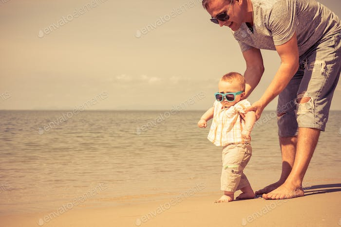 Father and baby son playing on the beach at the day time.