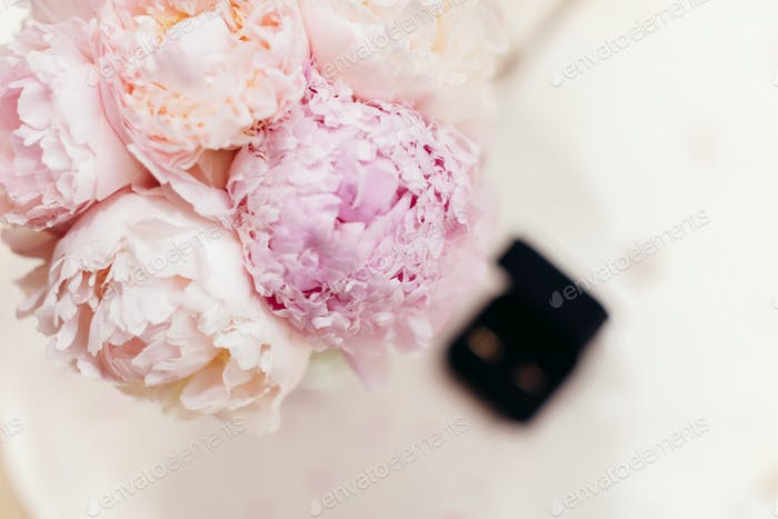 gentle wedding bouquet peonies with rings background