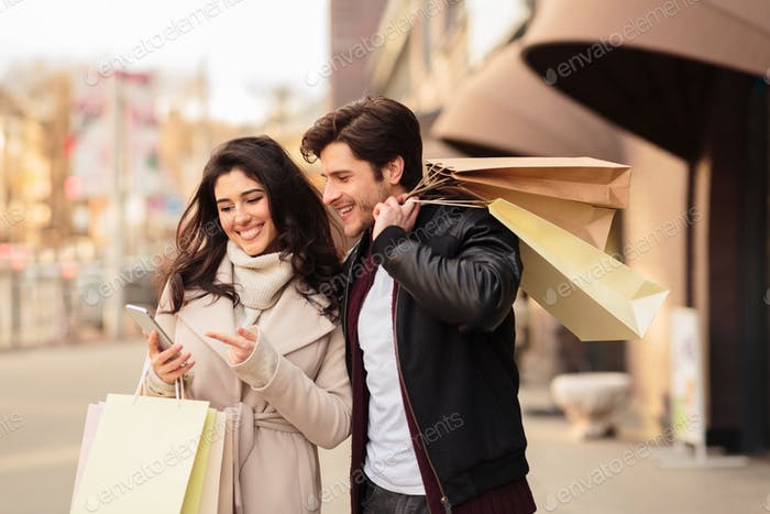 Order taxi online. Couple using smartphone after shopping