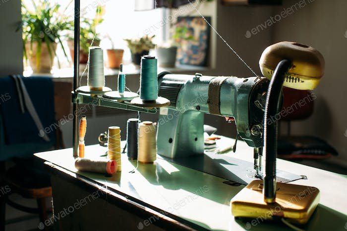 Sewing machine on table in factory in sun light. Small business, fashion designe, Tailor working