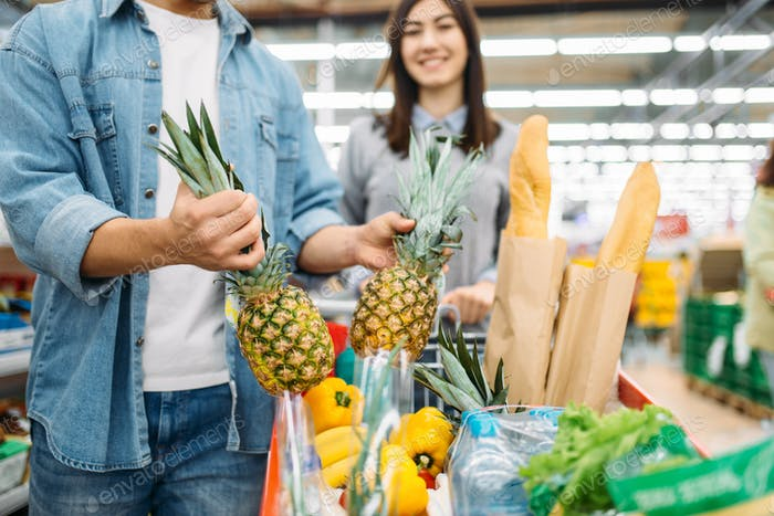 Couple puts pineapple into the cart in supermarket