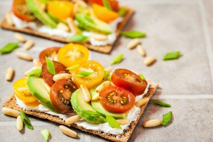 Сrisp bread toast  with cream cheese, fresh avocado, cherry tom