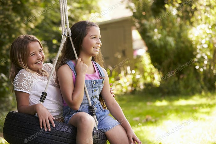 Side View Of Two Girls Playing On Tire Swing In Garden
