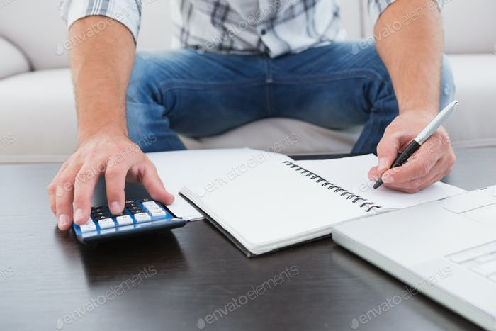 A businessman working on his finances at a table at his home