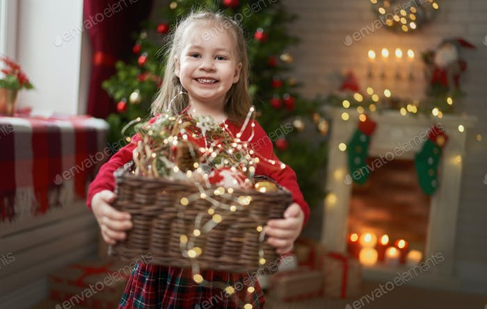 child with garlands near tree at home.