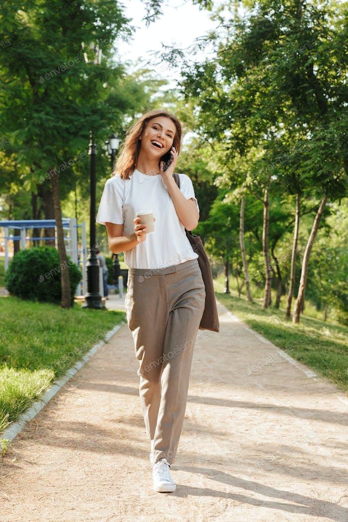 Full length image of caucasian modern woman walking down narrow