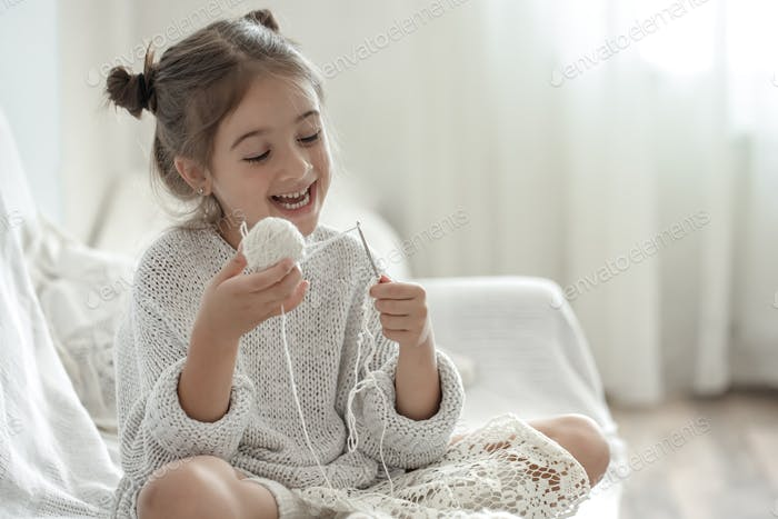 Cute little girl with threads learns to knit.