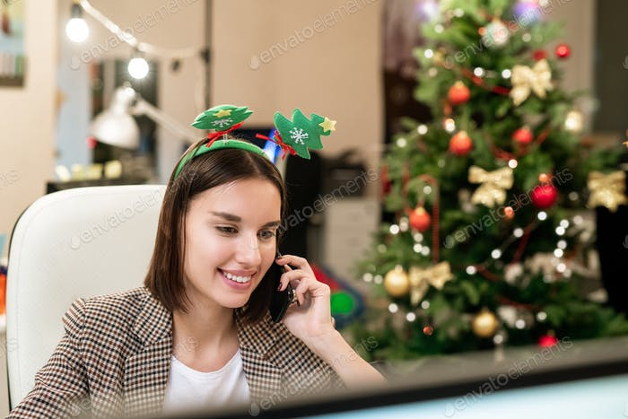 Young businesswoman congratulating clients on Christmas on mobile phone
