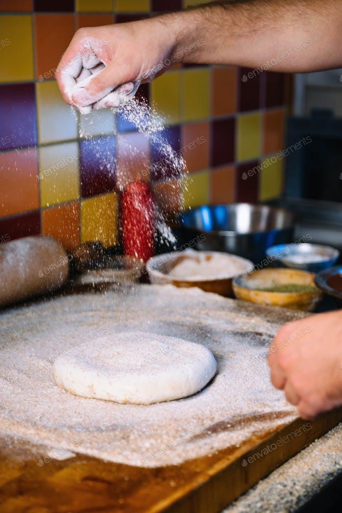 Hände Mehl verteilen und Teig für Pizza machen
