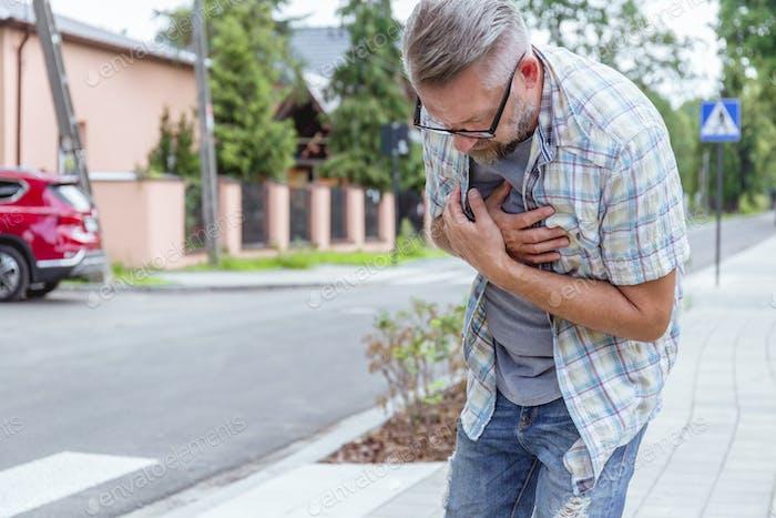 Mann im mittleren Alter mit einem Herzinfarkt auf der Straße