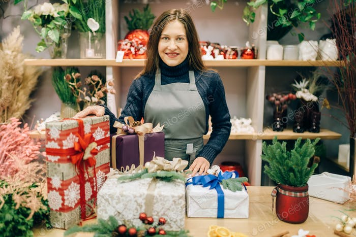 Seller with gift boxes in festive wrapping paper