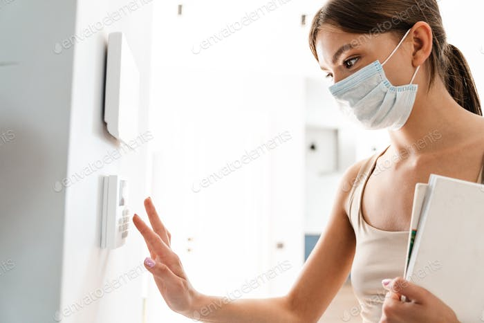 Young woman in medical mask entering code on keypad